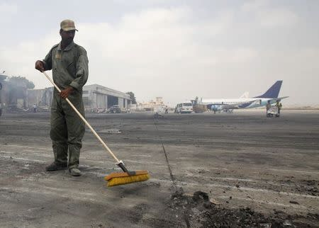 A man clears debris from the tarmac of Jinnah International Airport, after the attack by Taliban militants on Sunday, in Karachi in this June 10, 2014 file photo. REUTERS/Athar Hussain/Files