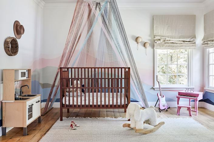 """<div class=""""caption""""> Duff's daughter Banks's nursery features a pastel mural and string installation by Laura Stewart. """"When I first found out I was having a girl, I thought I was going to be a lot cooler than I was. But then, all of a sudden, it turned into a pink explosion in there,"""" says Duff. """"Still, I have tried my best to keep it cool in there because I don't really know <em>who</em> she's going to grow up to be. Picking colors with Laura was a very fun, very collaborative process."""" The hat on the wall hangs in anticipation. When a pregnant Duff saw that one of her favorite cowboy hats came in a kids' version, she had to have it: """"I can't wait to be in a magic matching hats with my daughter!"""" </div>"""