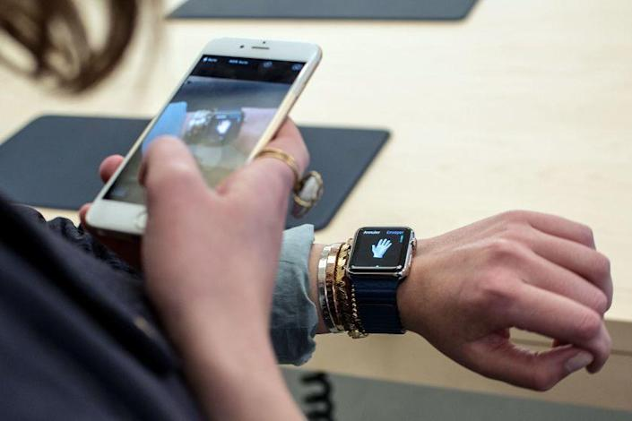 A customer uses an iPhone 6 smartphone to take a photo of a model of the Apple Watch
