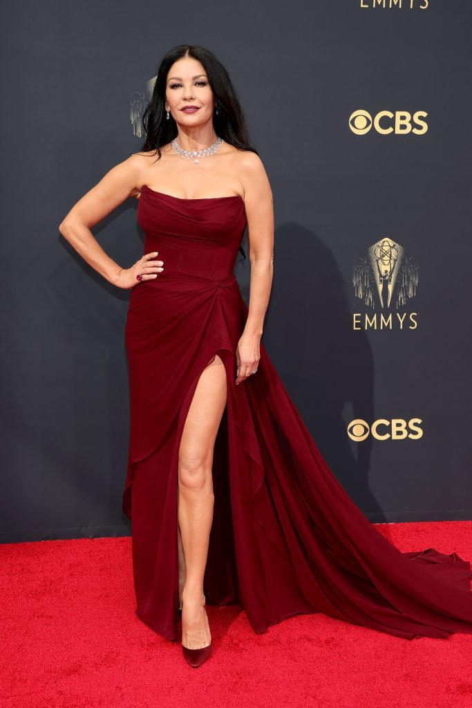 Catherine Zeta-Jones on the red carpet in a burgundy gown with a high slit