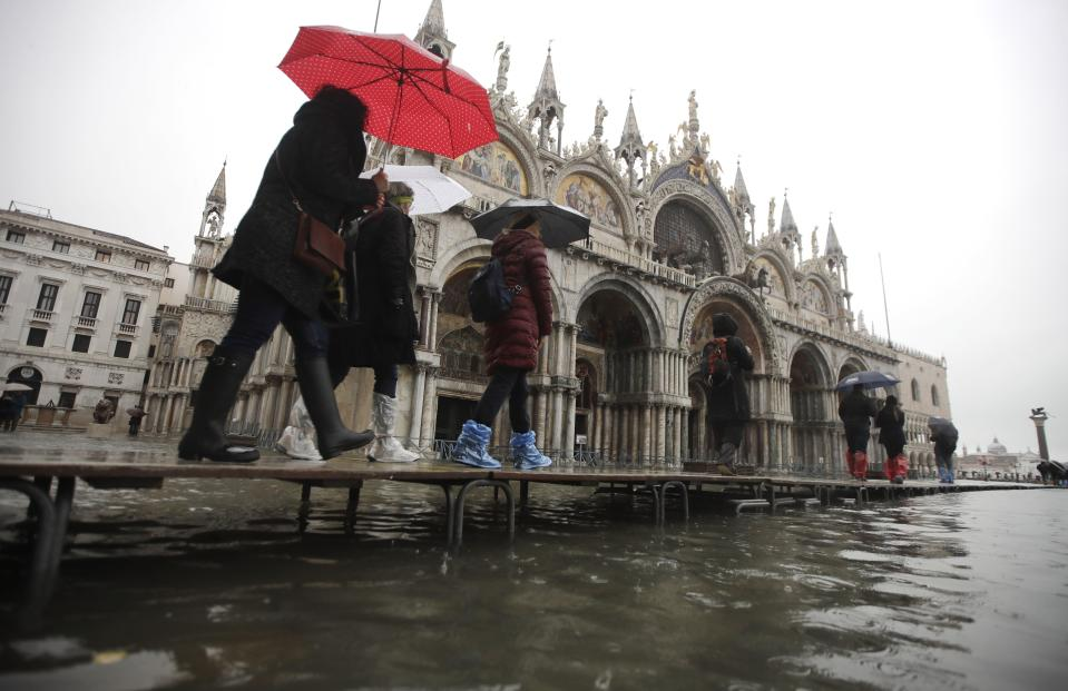 People walk on catwalk set up in front of St. Mark's Basilica on the occasion of a high tide, in a flooded Venice, Italy, Tuesday, Nov. 12, 2019. (Photo: Luca Bruno/AP)