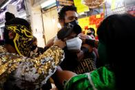 Lucha libre fighters encourage maskless Mexicans to wear masks at the Central Abastos market, in Mexico City