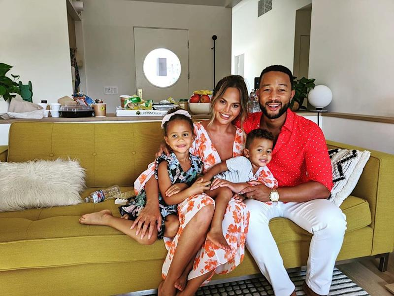 Chrissy Teigen, John Legend, Luna Legend and Miles Legend pose on a couch together
