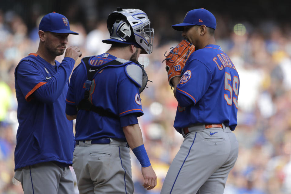 New York Mets' Carlos Carrasco (59) talks with Tomas Nido and pitching coach Jeremy Hefner, left, during the second inning of a baseball game against the Milwaukee Brewers, Sunday, Sept. 26, 2021, in Milwaukee. (AP Photo/Aaron Gash)