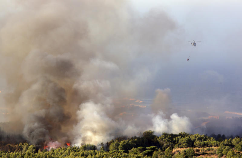 A firefighting helicopter flies above a forest fire burning at sunrise near the village of Charneca, in the Sintra national park, west of Lisbon, Sunday, Oct. 7, 2018. Over 700 firefighters were battling a forest fire that started overnight about 40 kilometers (25 miles) west of Lisbon. (AP Photo/Armando Franca)
