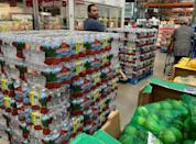 A worker wheeling a pallet of bottles back to their shelf was repeatedly stopped by new customers who grabbed what they could