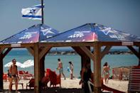 An Israeli flag flutters near shades with covers bearing the 2019 Eurovision Song Contest logo at a beach as the opening ceremony of the contest begins tonight, in Tel Aviv, Israel May 12, 2019. REUTERS/Ronen Zvulun