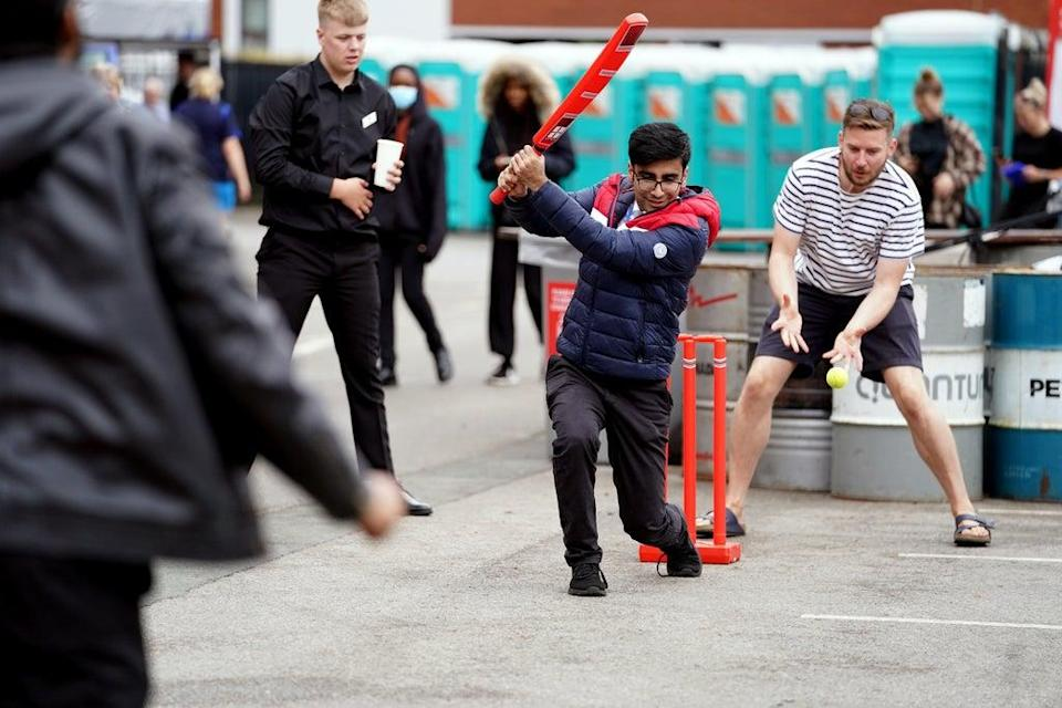 Fans play cricket outside of Old Trafford after the match was cancelled (Martin Rickett/PA) (PA Wire)