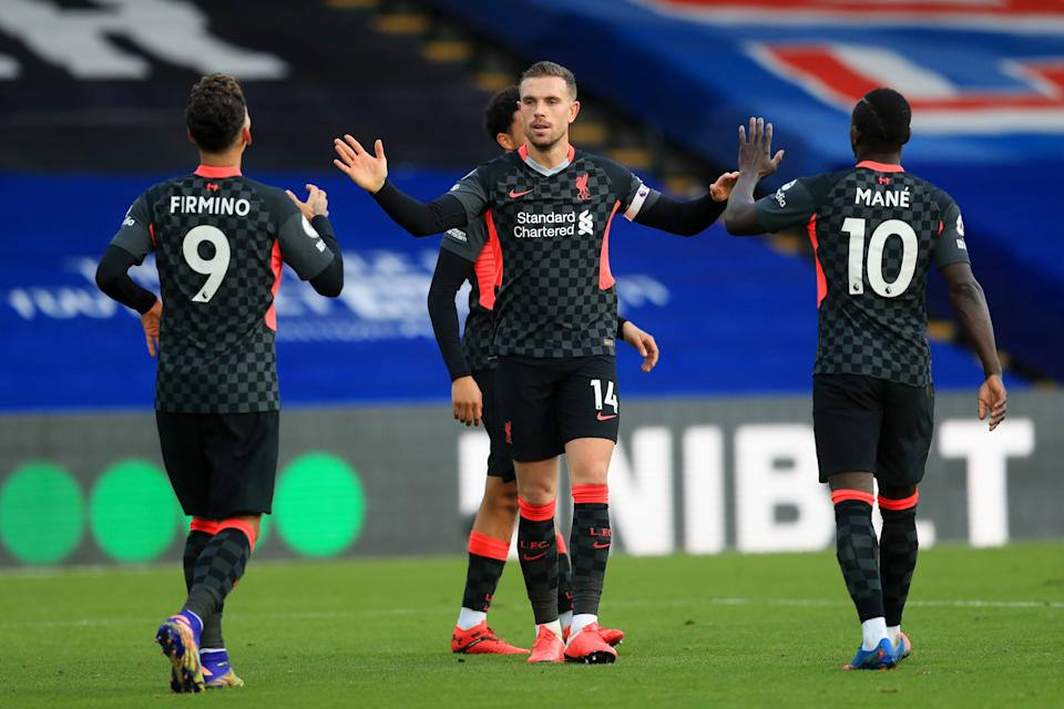 Liverpool captain Jordan Henderson (centre) celebrates with teammates Sadio Mane (right) and Roberto Firminho after scoring against Crystal Palace.