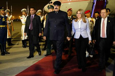 Venezuela's President Nicolas Maduro walks with his wife Cilia Flores upon their arrival at the airport in Beijing
