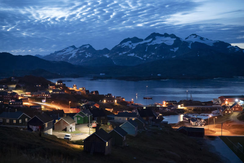 In this photo taken August 16, 2019, homes are illuminated after the sunset in Tasiilaq, Greenland. Source: AP Photo/Felipe Dana