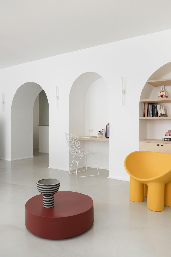 """<div class=""""caption""""> <strong>AFTER:</strong> One of the biggest changes to the home was this arched """"living wall"""" created by the architects. The yellow <a href=""""https://duplexdsgn.com/products/rolypoly7?variant=7399778058274"""" rel=""""nofollow noopener"""" target=""""_blank"""" data-ylk=""""slk:Roly Poly chair"""" class=""""link rapid-noclick-resp"""">Roly Poly chair</a> by Faye Toogood adds a pop of color to the living room furnished with a <a href=""""https://www.serax.com/en/round-fiber-coffee-table-marie-red-d68-h20"""" rel=""""nofollow noopener"""" target=""""_blank"""" data-ylk=""""slk:Serax coffee table"""" class=""""link rapid-noclick-resp"""">Serax coffee table</a> and vases by <a href=""""https://www.finnishdesignshop.com/AYTM-m-287.html"""" rel=""""nofollow noopener"""" target=""""_blank"""" data-ylk=""""slk:AYTM"""" class=""""link rapid-noclick-resp"""">AYTM</a> and <a href=""""https://lrnce.com/ceramics/vases/"""" rel=""""nofollow noopener"""" target=""""_blank"""" data-ylk=""""slk:LRNCE"""" class=""""link rapid-noclick-resp"""">LRNCE</a>. </div>"""