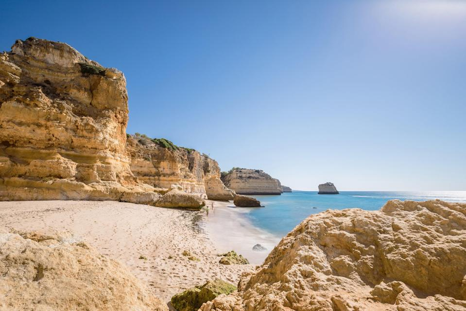 """With beautiful rocky outcrops and clean, calm water, Marinha is generally recognized as one of the <a href=""""https://www.cntraveler.com/galleries/2016-03-29/the-most-beautiful-beaches-in-spain-and-portugal?mbid=synd_yahoo_rss"""" rel=""""nofollow noopener"""" target=""""_blank"""" data-ylk=""""slk:best beaches"""" class=""""link rapid-noclick-resp"""">best beaches</a> in Portugal—and the world. Situated along Portugal's famously beautiful Algarve region, Praia da Marinha is known for its steep cliffs, soft sand, and calm waters ideal for snorkeling."""