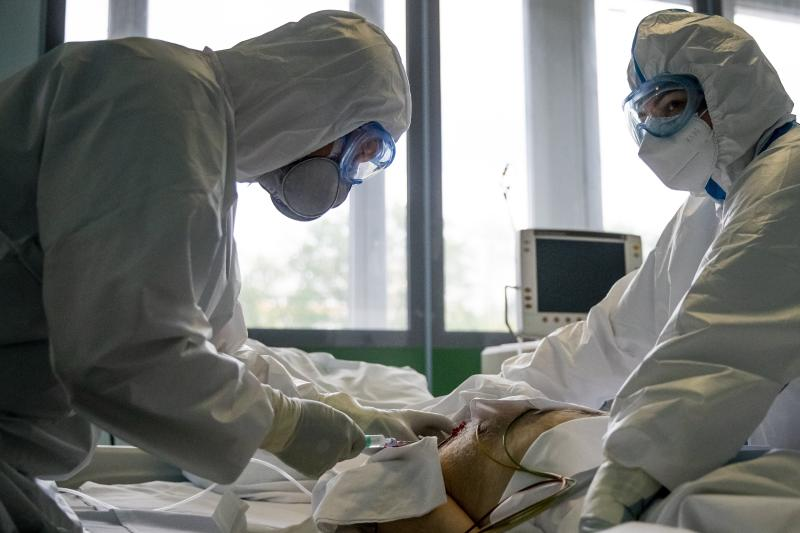 In this photo taken on Friday, May 15, 2020, Dr. Osman Osmanov, left, and his colleagues treat a coronavirus patient on artificial lung respiration at an intensive care unit of the Filatov City Clinical Hospital in Moscow, Russia. Moscow accounts for about half of all of Russia's coronavirus cases, a deluge that strains the city's hospitals and has forced Osmanov to to work every day for the past two months, sometimes for 24 hours in a row. (AP Photo/Pavel Golovkin)