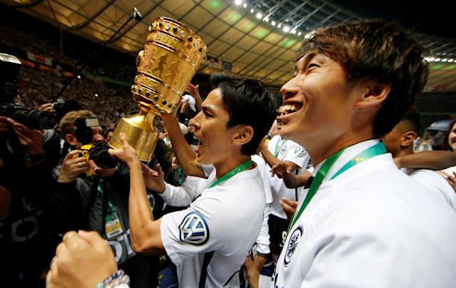 Soccer Football - DFB Cup Final - Bayern Munich vs Eintracht Frankfurt - Olympiastadion, Berlin, Germany - May 19, 2018 Eintracht Frankfurt's Makoto Hasebe and Daichi Kamada celebrate with the trophy after winning the DFB Cup REUTERS/Axel Schmidt DFB RULES PROHIBIT USE IN MMS SERVICES VIA HANDHELD DEVICES UNTIL TWO HOURS AFTER A MATCH AND ANY USAGE ON INTERNET OR ONLINE MEDIA SIMULATING VIDEO FOOTAGE DURING THE MATCH.