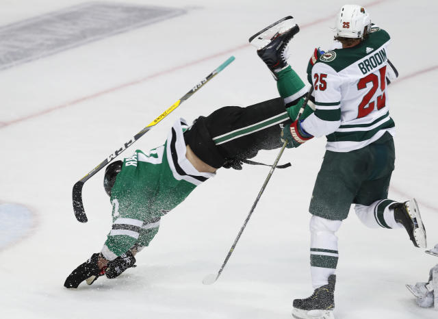 Dallas Stars right wing Alexander Radulov (47) is knocked off his feet by Minnesota Wild defenseman Jonas Brodin (25) during the first period of an NHL hockey game in Dallas, Friday, Feb. 1, 2019. (AP Photo/LM Otero)