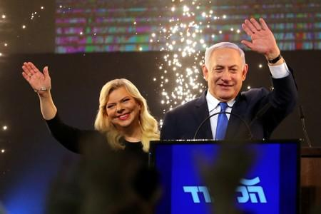 FILE PHOTO: Israeli Prime Minister Benjamin Netanyahu and his wife Sara wave as Netanyahu speaks following the announcement of exit polls in Israel's parliamentary election at the party headquarters in Tel Aviv, Israel