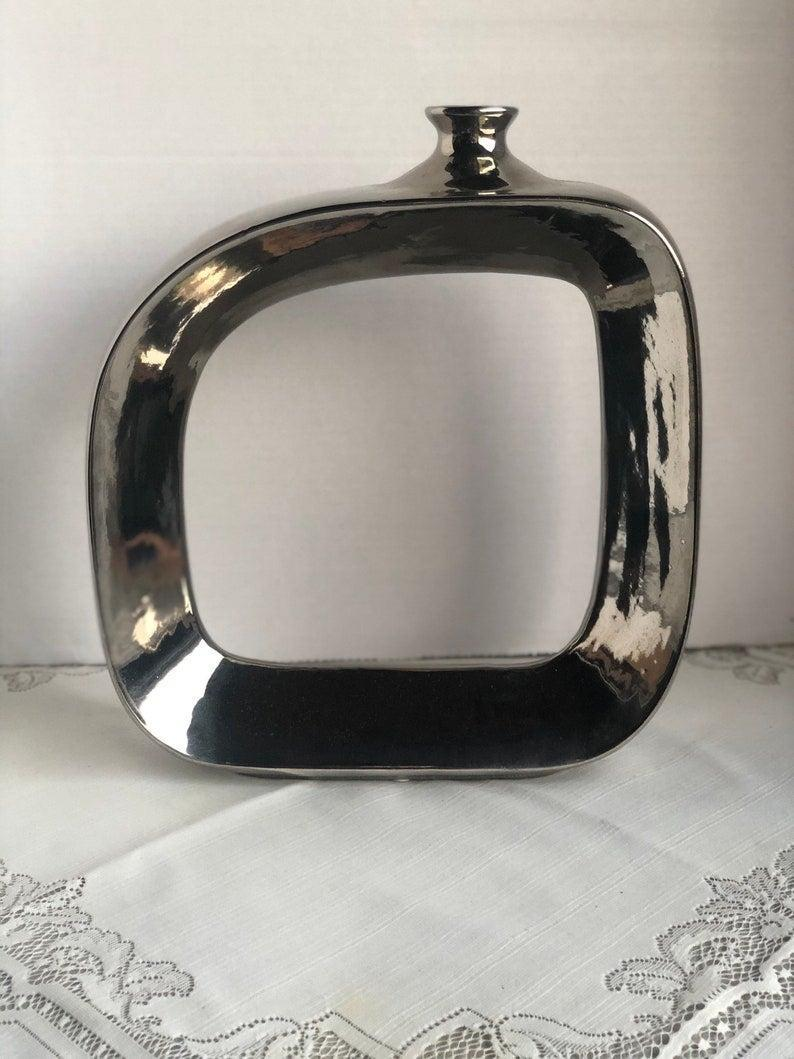 """The outline vase may seem like a particularly modern iteration of minimalism but you can always find a vintage inspiration. In this case, the chrome-heavy, geometric '80s!<br><br><strong>VintagevengeanceShop</strong> Vintage Silver Square Hollow Vase #136, $, available at <a href=""""https://www.etsy.com/uk/listing/886993506/vintage-silver-square-hollow-vase-136"""" rel=""""nofollow noopener"""" target=""""_blank"""" data-ylk=""""slk:Etsy"""" class=""""link rapid-noclick-resp"""">Etsy</a>"""