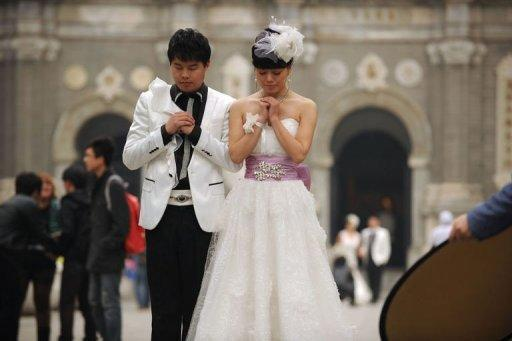 """Couples pose for wedding photos in Beijing, on November 11. Chinese couples flocked to registry offices to marry in the belief that the """"11/11/11"""" date is the most auspicious in a century"""