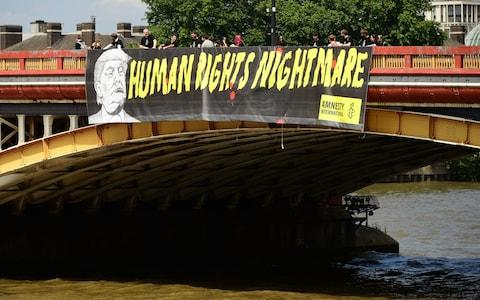 Amnesty International unveil a banner on the Vauxhall Bridge in London - Credit: Ian West /PA