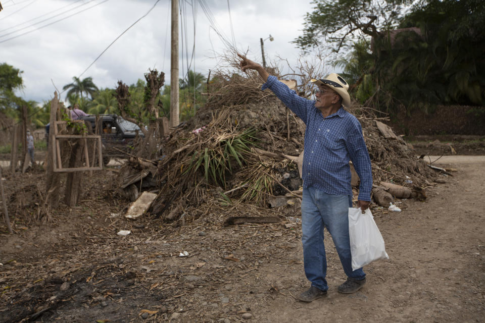 Juan Antonio Ramirez, 73, points to a tree that was hit by the floods during last year's hurricanes Eta and Iota in the San Jose neighborhood of La Lima, on the outskirts of San Pedro Sula, Honduras, where banana and sugar cane workers live, Monday, Jan. 11, 2021. Ramirez's children and grandchildren were among some 30 people who spent six days stranded on a corrugated metal roof surrounded by floodwaters in November. (AP Photo/Moises Castillo)