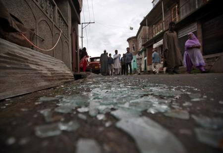 Kashmiris walk past broken window glass after clashes between protesters and the security forces on Friday evening, in Srinagar