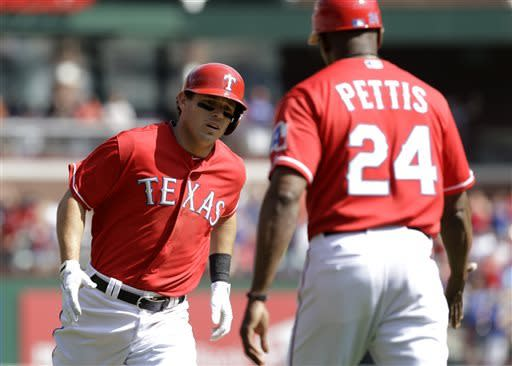 Texas Rangers' Ian Kinsler, left, is congratulated by third base coach Gary Pettis (24) following Kinsler's solo home run off of Los Angeles Angels' Tommy Hanson in the third inning of a baseball game Saturday, April 6, 2013, in Arlington, Texas. (AP Photo/Tony Gutierrez)