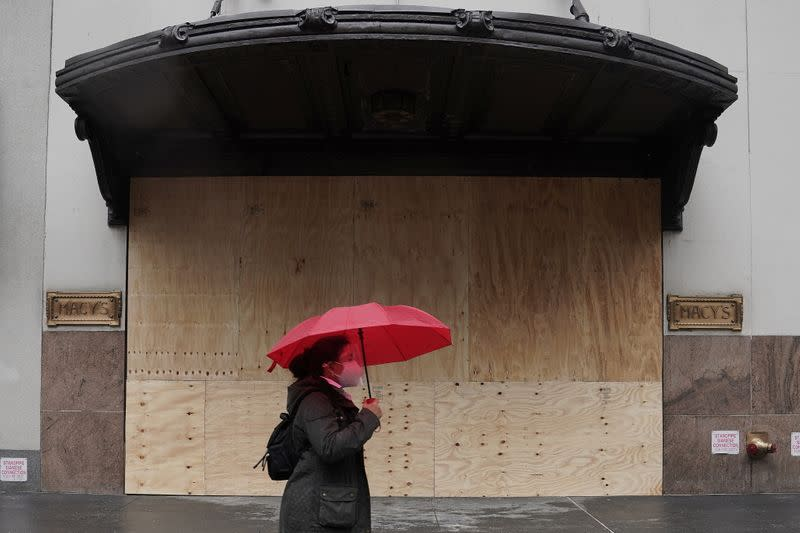 A woman walks past a Macy's department store that has had sheets of plywood