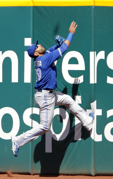 Toronto Blue Jays right fielder Jose Bautista climbs the wall trying to catch a two-run home run by Cleveland Indians' Jason Kipnis in the fifth inning of a baseball game in Cleveland on Saturday, April 7, 2012. (AP Photo/Amy Sancetta)
