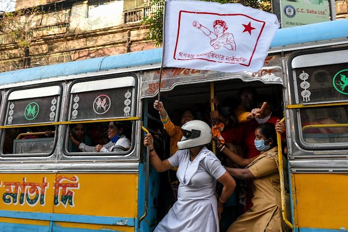 women spill out of a bus holding protest flags and chanting.