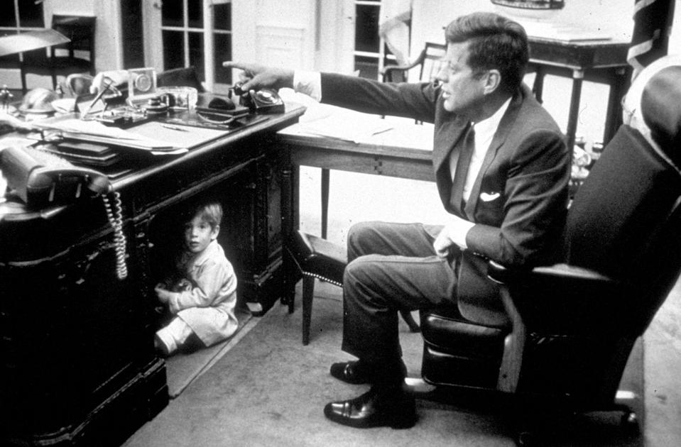 <p>President John F. Kennedy is pictured in the Oval Office while his son, John F. Kennedy, Jr., played under his desk.</p>