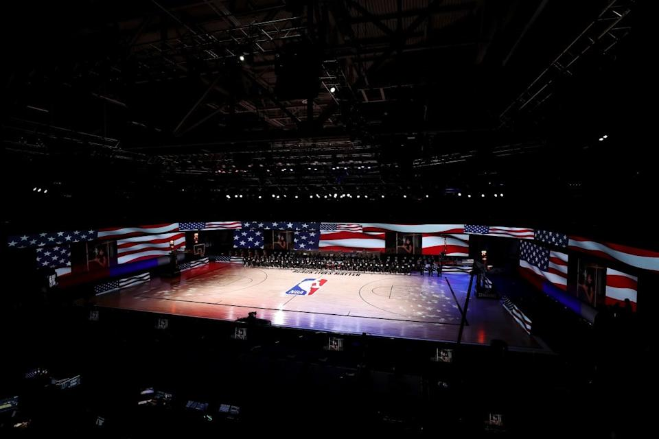 """<div class=""""inline-image__caption""""><p>Players, coaches and staff kneel during the national anthem before the game between the Houston Rockets and the Dallas Mavericks at The Arena at ESPN Wide World of Sports Complex on July 31, 2020, in Lake Buena Vista, Florida. </p></div> <div class=""""inline-image__credit"""">Mike Ehrmann/Getty</div>"""
