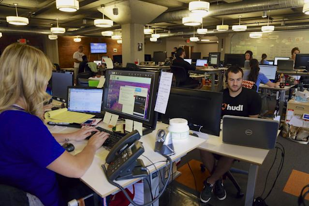 In this photo from Aug. 14, 2014, support team members work at their stations at Hudl, in Lincoln, Neb. Hudl is a software company that has developed a way to immediately get game film to coaches after games and break down and separate different plays by type. (AP Photo/Nati Harnik)