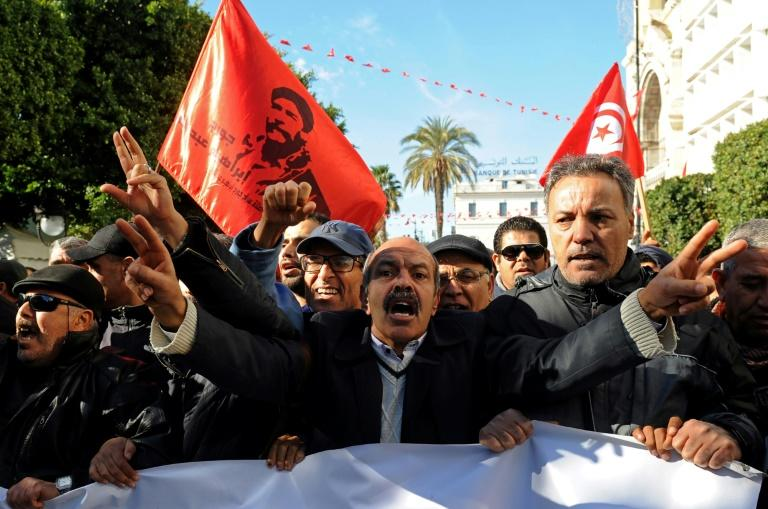 Protesters shout anti-government slogans outside the Tunisian General Labour Union headquarters on the seventh anniversary of the 2011 uprising