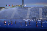 Members of the Canadian men's field hockey team run beneath sprinklers during a training session at Oi Hockey Stadium ahead of the the 2020 Summer Olympics, Thursday, July 22, 2021, in Tokyo, Japan. (AP Photo/John Locher)