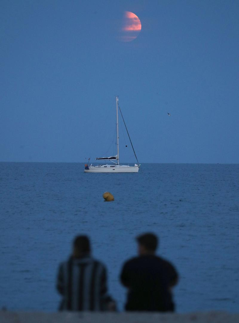 People watch on as the moon rises over a boat moored off of Avon beach in Dorset (PA)