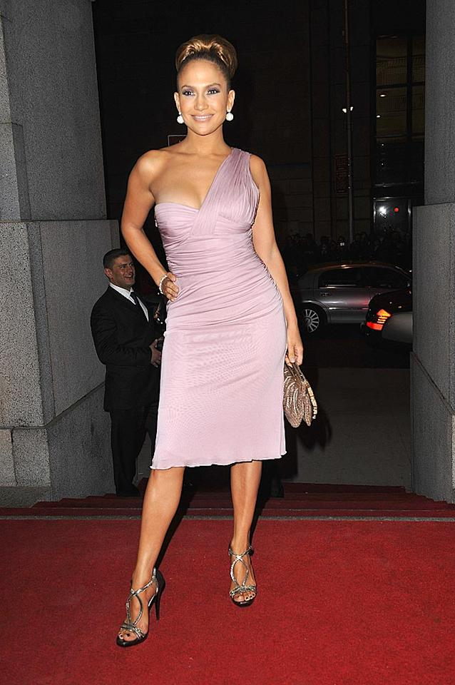 """Jennifer Lopez looked absolutely stunning in a lavender Versace one-shoulder dress at the Fashion Group's 25th Annual Night of Stars in NYC. The diva's $2,000 Versace faux croc clutch and severely slicked back 'do were the perfect accessories for the A-list event. SGP Italia srl/<a href=""""http://www.wireimage.com"""" target=""""new"""">WireImage.com</a> - October 23, 2008"""