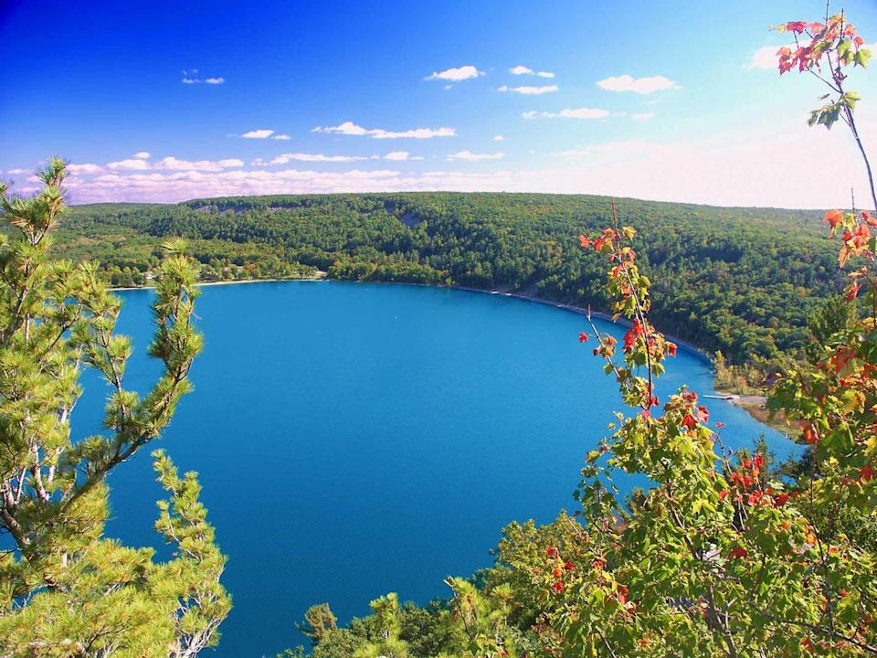 """<p><strong>Devil's Lake State Park </strong></p><p><a href=""""https://dnr.wi.gov/topic/parks/name/devilslake/"""" rel=""""nofollow noopener"""" target=""""_blank"""" data-ylk=""""slk:Devil's Lake State Park"""" class=""""link rapid-noclick-resp"""">Devil's Lake State Park</a> is the largest state park in Wisconsin, located south of Baraboo. The park is known for its 500 foot high quartzite bluffs along the 360 acre Devil's Lake, which was a result of a glacier depositing terminal moraines that plugged the north and south ends of the gap in the bluffs during the last ice age 12,000 years ago! Visitors enjoy hiking and camping overnight, taking in the history and views.</p>"""