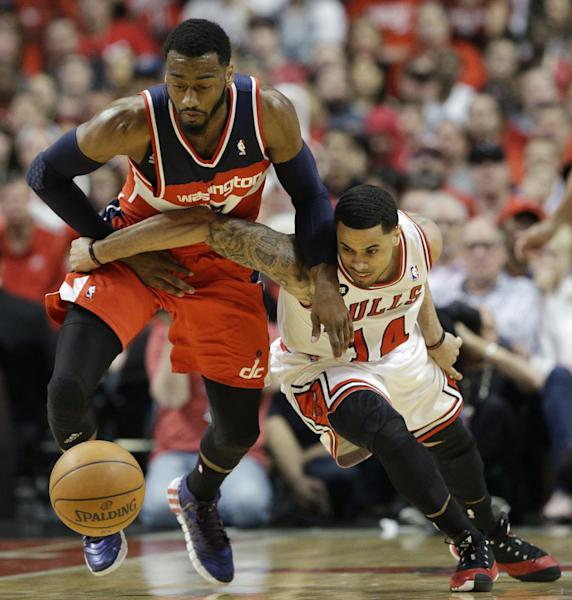Washington Wizards guard John Wall, left, steals the ball from Chicago Bulls guard D.J. Augustin during the first half in Game 1 of an opening-round NBA basketball playoff series in Chicago, Sunday, April 20, 2014. (AP Photo/Nam Y. Huh)