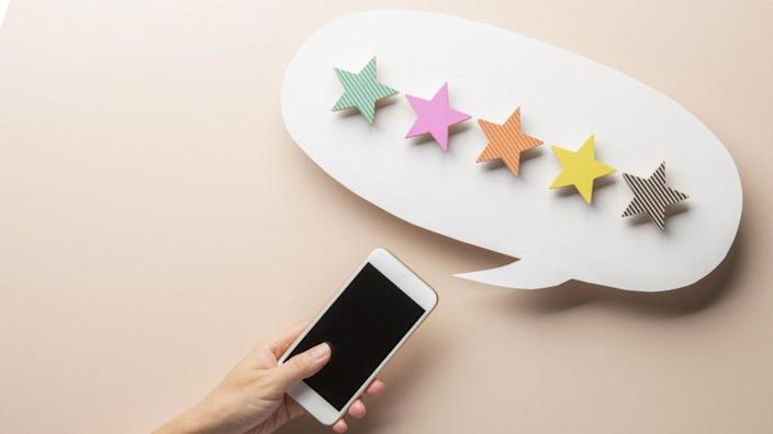Five-star reviews made out of wooden blocks appear to pop out of a smartphone