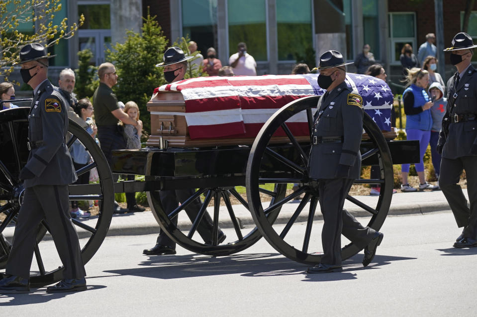 A processional approaches the Holmes Convocational Center for the funeral services of Watauga County Sheriff's Deputies Sgt. Chris Ward and K-9 Deputy Logan Fox in Boone, N.C., Thursday, May 6, 2021. The two deputies were killed in the line of duty. (AP Photo/Gerry Broome)