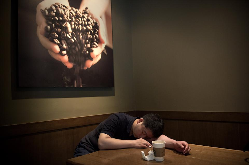 A man takes a nap after drinking a coffee inside a Starbucks in Beijing on June 28, 2017. / AFP PHOTO / NICOLAS ASFOURI        (Photo credit should read NICOLAS ASFOURI/AFP via Getty Images)