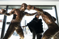 Weatta Frazier Collins kisses a statue of her father Joe Frazier, right, fighting Muhammad Ali, on the 50th anniversary of the boxers' World Heavyweight championship boxing bout, at the Joe Hand Gym in Feasterville, Pa., Monday, March 8, 2021. (AP Photo/Matt Rourke)