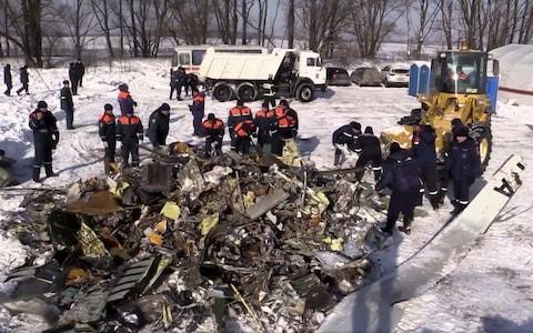 Russian Emergency Situations Ministry workers collect wreckage from the fallen plane