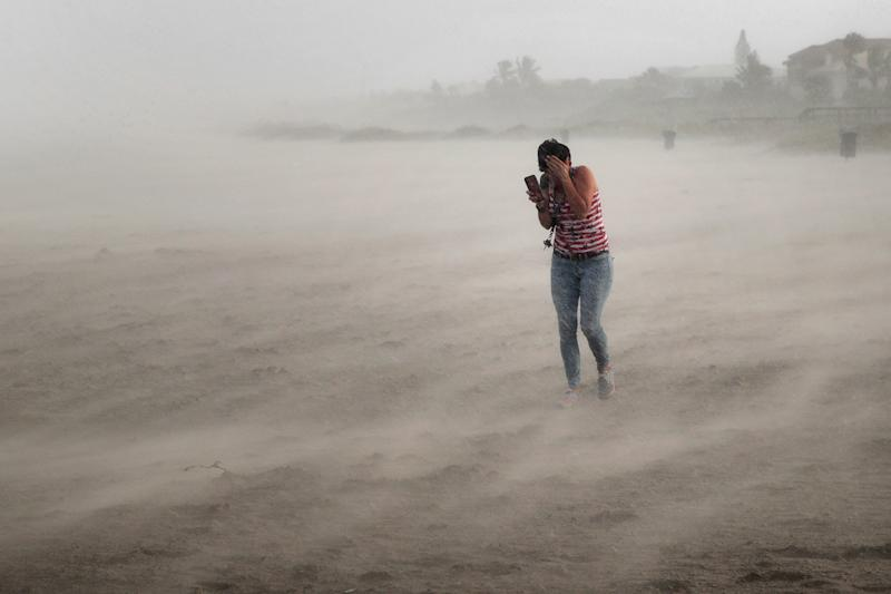 A woman seeks cover from wind, blowing sand and rain whipped up by Hurricane Dorian as she walks on the beach on Sept. 2, 2019 in Cocoa Beach, Fla. (Photo: Scott Olson/Getty Images)