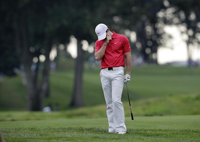 Rory McIlroy, of Northern Ireland, reacts to hitting into a sand trap on the 13th hole during the first round of play at The Barclays golf tournament Thursday, Aug. 21, 2014, in Paramus, N.J. (AP Photo/Mel Evans)