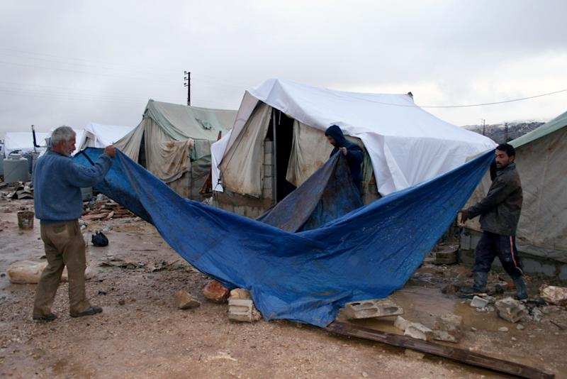 "Syrian refugees cover their tent with a tarp as a heavy snowstorm batters the region, in the Bekaa valley, eastern Lebanon, Wednesday, Dec. 11, 2013. The United Nations refugee agency says it is ""extremely concerned"" for hundreds of thousands of Syrian refugees scattered across the region amid a snow storm with high winds and torrential rains. (AP Photo/Shibli Abi-Assi)"
