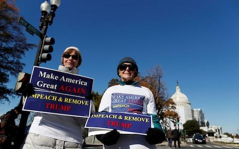 Protesters hold placards outside of the Longworth building, where the hearing took place - Credit: Reuters