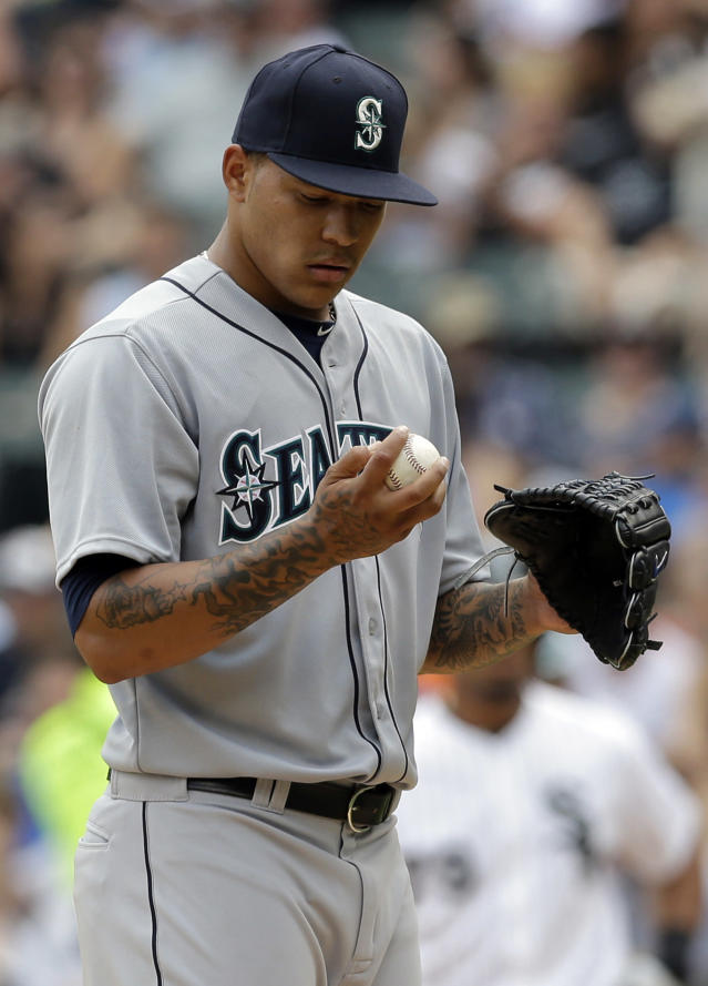 Seattle Mariners starter Taijuan Walker checks the ball after Chicago White Sox's Jose Abreu hit a single during the first inning of a baseball game in Chicago, Sunday, July 6, 2014. The White Sox won 1-0. (AP Photo/Nam Y. Huh)