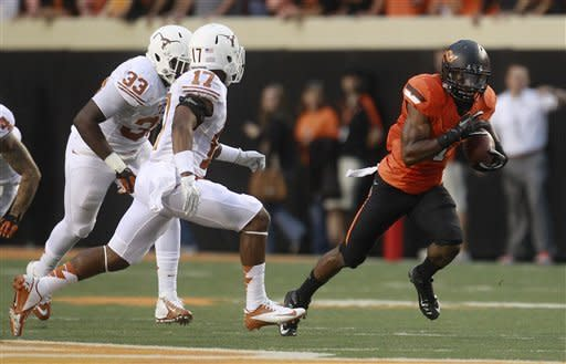 Oklahoma State running back Joseph Randle (1) eludes Texas' Steve Edmond (33) and Adrian Phillips (17) and takes off on a 69-yard touchdown run in the first quarter of an NCAA college football game in Stillwater, Okla., Saturday, Sept. 29, 2012. (AP Photo/Sue Ogrocki)